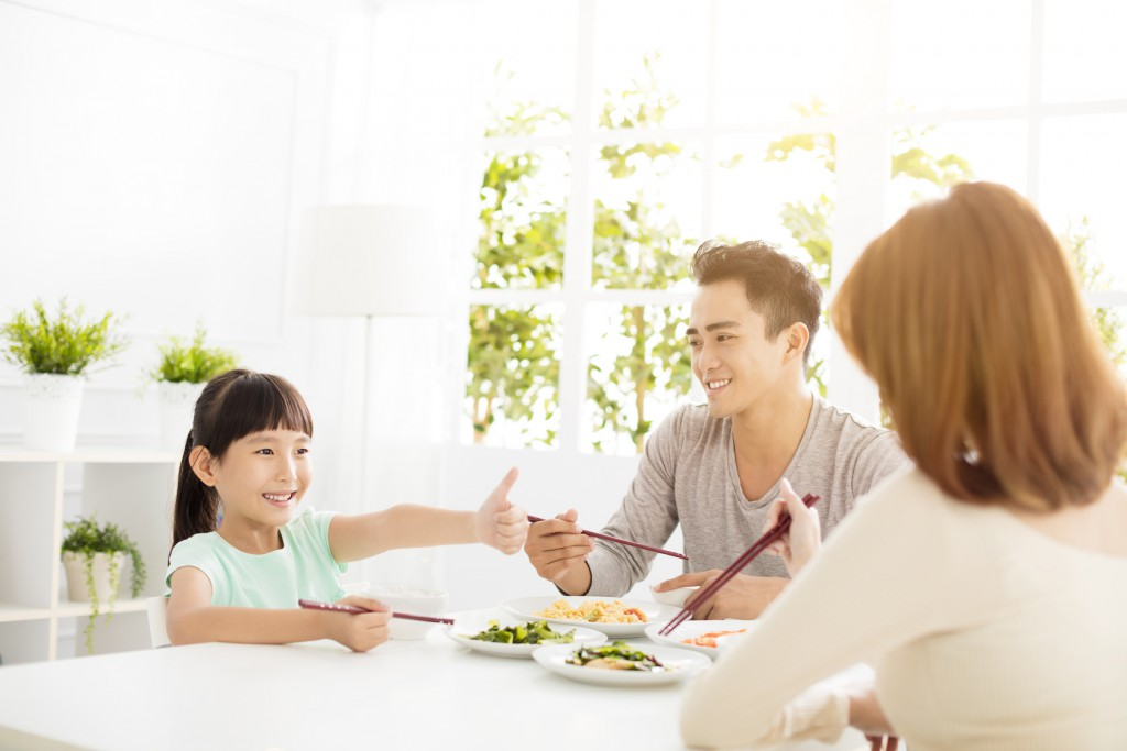 daughter gives mother  thumbs up for the delicious dinner
