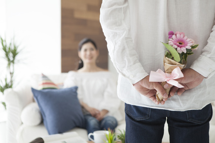 The man is hiding a bouquet of flowers behind