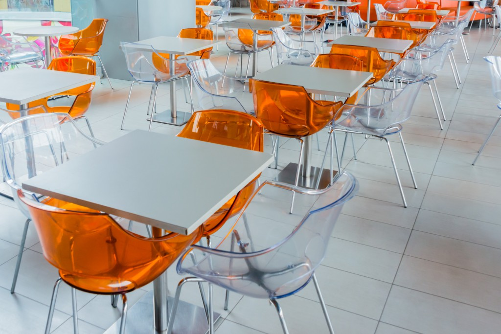 Orange plastic chairs and a white table on food court in mall.