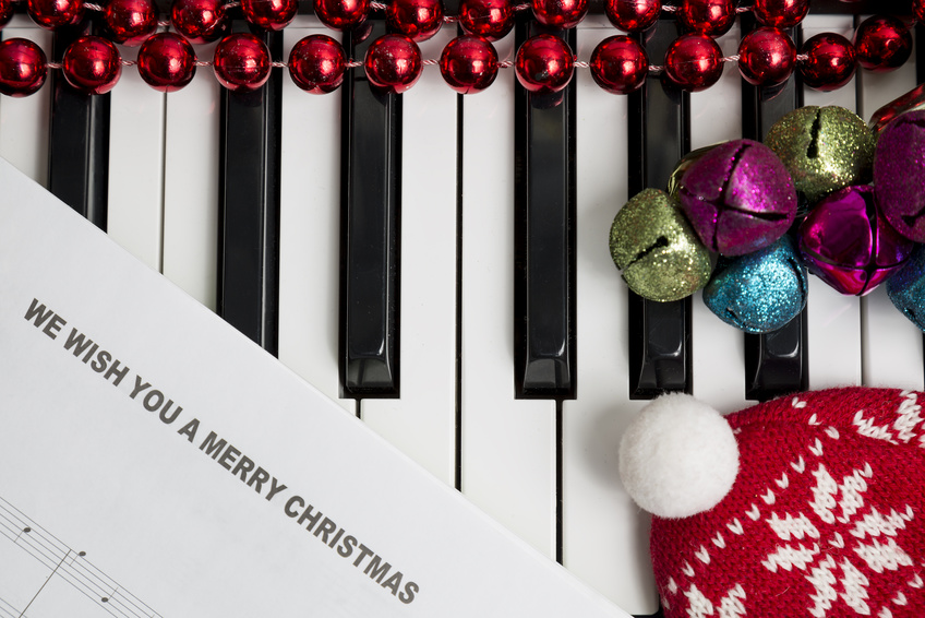 Christmas music concept. Printed music on the pianto with jingle bells, red christmas balls and hat.